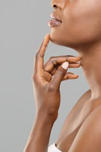 Chin augmentation. Unrecognizable afro woman touching implant in her face, happy with result of plastic surgery, gray background with free space